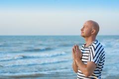 L'homme se tient prêt la mer et prie à Dieu Image stock