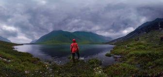 L'homme se tient prêt le lac dans la veste rouge dans le panorama nuageux de temps photo stock