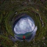 L'homme se tient prêt le lac dans la veste rouge par temps nuageux planète minuscule 360 photographie stock libre de droits