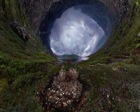 L'homme se tient prêt le lac dans la veste rouge par temps nuageux planète minuscule 360 photographie stock