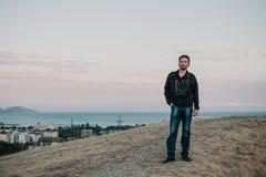 L'homme se tient sur la colline sur le fond de la mer et du ciel Image libre de droits