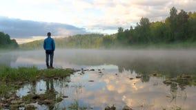L'homme se tient sur la pierre contre le brouillard de propagation au-dessus de l'eau calme banque de vidéos
