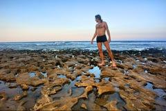 L'homme se tient sur la plage rocheuse Image stock