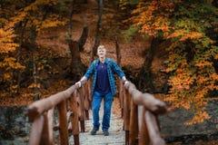 L'homme se tient sur le pont en bois dans la for?t d'automne images stock