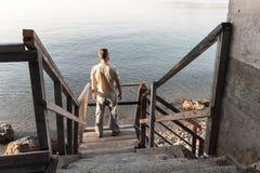 L'homme se tient sur le vieil escalier en bois Photographie stock