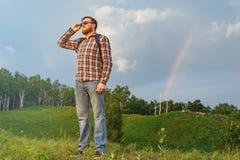L'homme se tient sur une colline et observer le coucher du soleil Image libre de droits