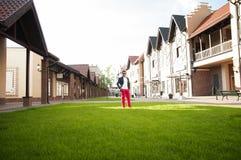L'homme se tient sur une pelouse verte des maisons de cottage Photographie stock