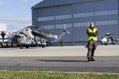 L'homme se tient sur une piste avec l'hélicoptère tchèque du mil Mi-171Sh de militaires à l'arrière-plan Images stock