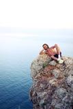 L'homme se trouve sur une montagne et un repos photographie stock libre de droits