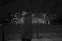 L'homme seul marche après des maisons la nuit Photographie stock libre de droits