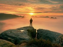 L'homme seul se tient sur la crête de la roche Randonneur observant à l'automne Sun à l'horizon Beau moment le miracle de la natu image stock