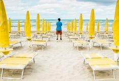 L'homme seul se tient sur la plage vide et regarde au Photos stock