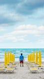 L'homme seul se tient sur la plage vide et regarde au Image stock