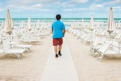 L'homme seul se tient sur la plage vide et regarde au Images stock