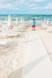 L'homme seul se tient sur la plage vide et regarde au Photo stock