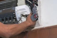 L'homme simple d'électricien propre, la difficulté et maintiennent la climatisation photo libre de droits