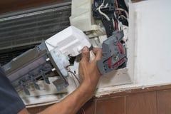 L'homme simple d'électricien propre, la difficulté et maintiennent la climatisation photo stock