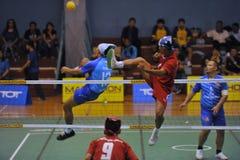 L'homme sont haut bloquant la boule par le filet dans le jeu du volleyball de coup-de-pied, takraw de sepak images stock