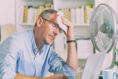 L'homme souffre de la chaleur dans le bureau ou à la maison images libres de droits
