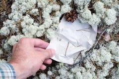L'homme soulève la page blanche du blanc dans la forêt Image stock