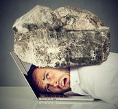 L'homme soumis à une contrainte avec la tête a serré entre l'ordinateur portable et la roche images stock