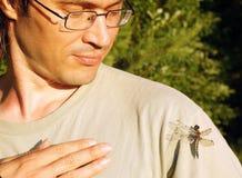 L'homme sourit amical à la libellule photo stock