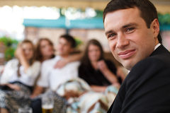 L'homme sourit au-dessus de son épaule entourée par des amis photo libre de droits