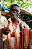 L'homme sourit pendant qu'il vend des perles du côté de la route Photo libre de droits