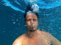 L'homme sous l'eau descend pour baser et libère des bulles de l'oxygène photo libre de droits