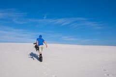 L'homme sportif avec un surf des neiges monte la dune de sable Photos stock