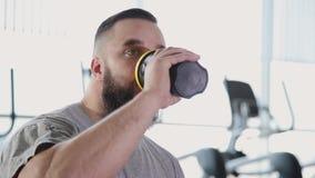L'homme sportif bel ouvre un dispositif trembleur et des boissons de protéine au gymnase banque de vidéos