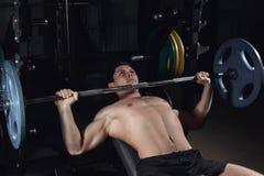 L'homme sportif brutal pompant muscles sur le banc à presse photos libres de droits
