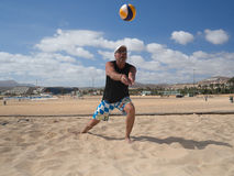L'homme sportif drague le beachvolleyball photo stock