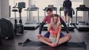 L'homme sportif et attirant aide une belle femme à s'étirer sur le plancher dans le gymnase banque de vidéos