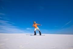 L'homme sportif monte sur le surf des neiges dans les dunes de sable Image libre de droits