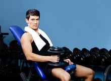 L'homme sportif se repose retenant un poids dans la main Photographie stock libre de droits