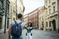 L'homme suivent la femme dehors à la vieille rue europian Photographie stock