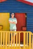L'homme supérieur avec des bras a croisé la balustrade se tenante prêt de la hutte de plage Photo libre de droits