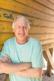 L'homme supérieur avec des bras a croisé la hutte se tenante prêt de plage Images stock