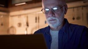 L'homme supérieur avec des verres travaillent sur l'ordinateur portable du maison-bureau la nuit L'homme d'affaires a mis dessus  banque de vidéos
