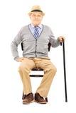 L'homme supérieur décontracté s'asseyant sur une chaise en bois et regardant est venu image libre de droits