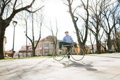 L'homme supérieur dans le bleu a vérifié la chemise avec la bicyclette en ville Photos stock