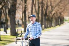 L'homme supérieur dans le bleu a vérifié la chemise avec la bicyclette en ville Image libre de droits