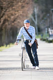 L'homme supérieur dans le bleu a vérifié la chemise avec la bicyclette en ville Images stock