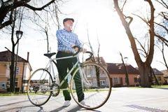L'homme supérieur dans le bleu a vérifié la chemise avec la bicyclette en ville Photographie stock