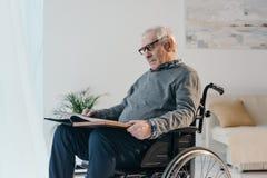 L'homme supérieur dans le fauteuil roulant regarde vieux image stock