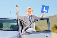 L'homme supérieur de sourire posant à côté de sa voiture tenant un L signent et c Image stock
