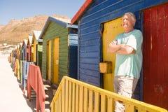L'homme supérieur heureux avec des bras a croisé la position à la hutte de plage Photographie stock libre de droits