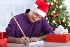 L'homme supérieur heureux de sourire écrit des souhaits au père noël Image libre de droits