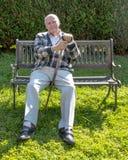L'homme supérieur a plaisir à s'asseoir sur un banc dans son jardin photos stock